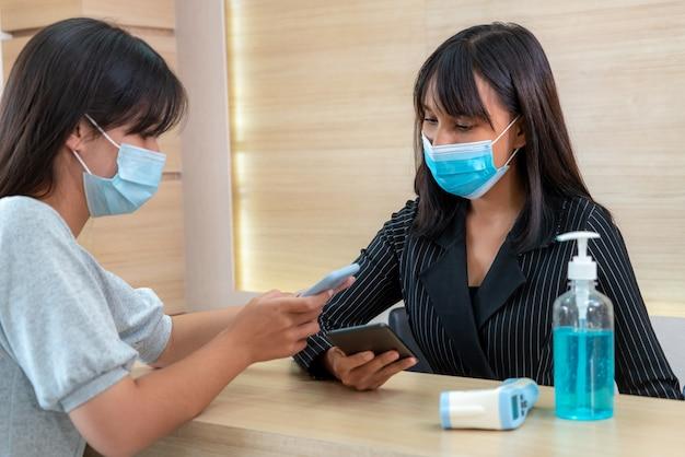 Регистратор и гость в маске на стойке регистрации во время разговора в офисе или больнице