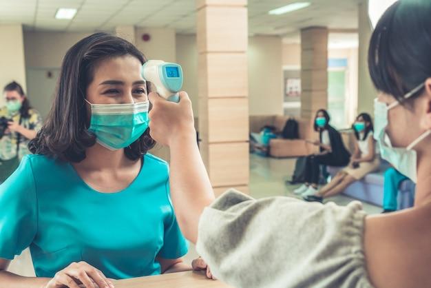 フロントデスクでフェイスマスクを着用している受付係とゲスト。