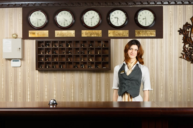 Receptionist at counter desk of modern hotel