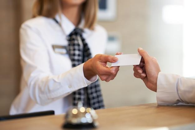 Портье дает ключ-карту бизнесвумен на стойке регистрации отеля