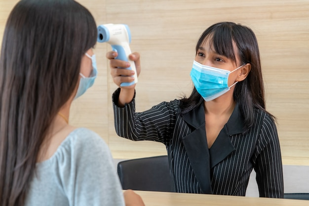 Receptionist and guest wearing face mask at front desk while having conversation in office or hospital