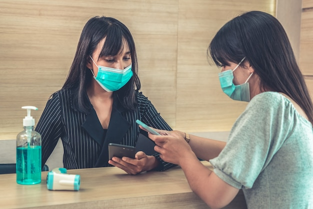 Receptionist and guest wearing face mask at front desk .