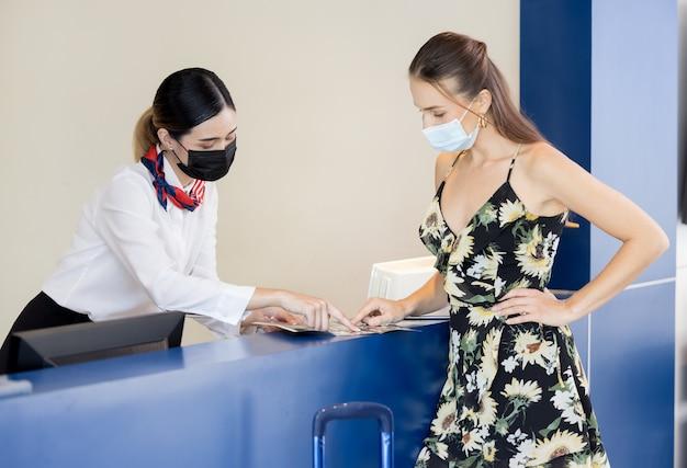 受付係がフロントデスクで観光客にパスポートを渡し、ホステルの受付