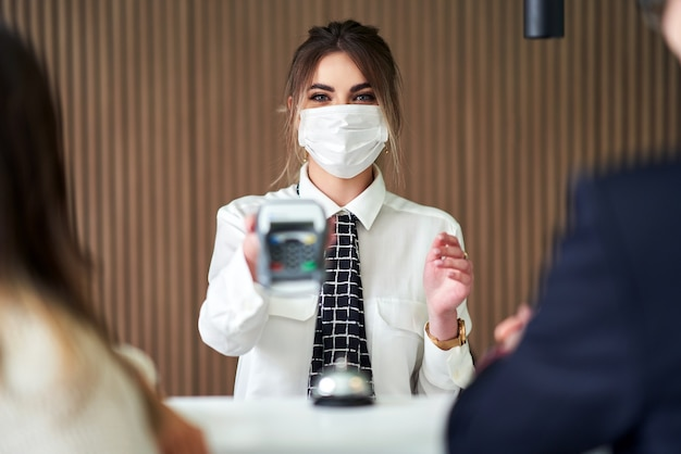 ホテルで働くマスクの受付係