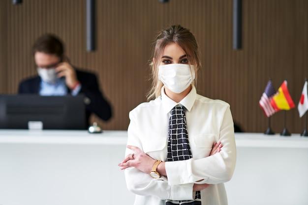 ホテルで働いているcovid-19のためにマスクを身に着けている受付係