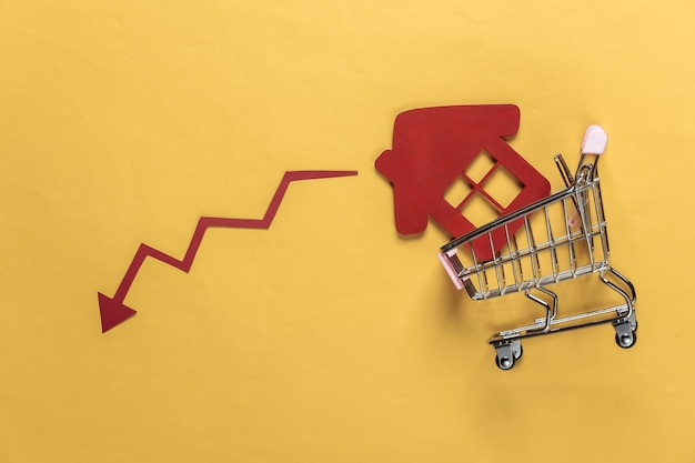 Recession of sales and purchases of housing shopping trolley with a house, drop arrow on a yellow