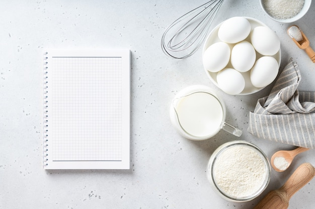 Recipe book and bakery ingredients on a white table view from above