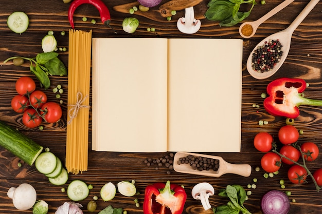 A recipe book is opened on a wooden table, with ingredients for italian dishes laid out