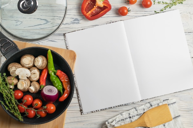 Recipe book with fresh organic ingredients in frying pan