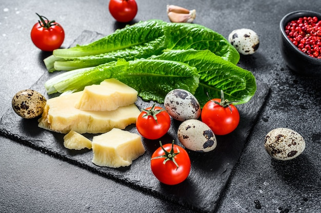 Recipe for caesar salad, romaine lettuce, tomatoes, eggs, parmesan, garlic, pepper. black background. top view.