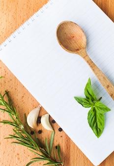 Концепция рецепта. чистый лист бумаги на деревянной доске со специями