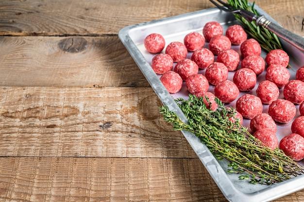 주방 쟁반에 백리향과 로즈마리를 곁들인 갈은 소고기 미트볼 요리법. 나무 배경입니다. 평면도. 공간을 복사합니다.