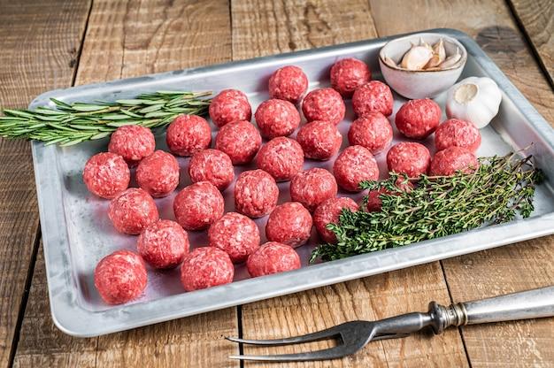 주방 쟁반에 백리향과 로즈마리를 곁들인 갈은 소고기 미트볼 요리법. 나무 배경입니다. 평면도.