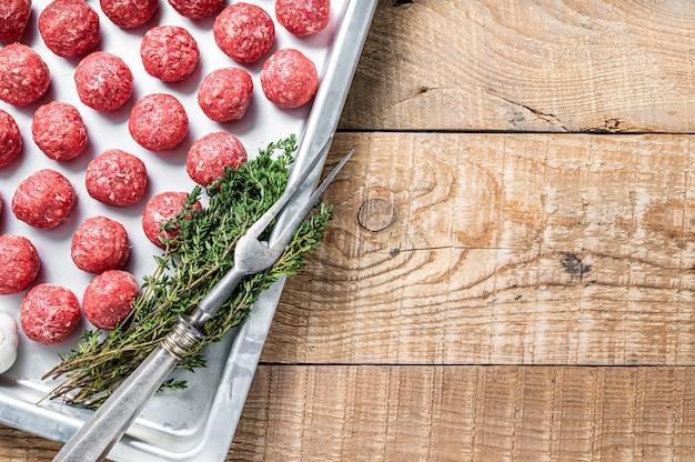 Рецепт приготовления фрикаделек из говяжьего фарша с тимьяном и розмарином на кухонном подносе. деревянный фон.