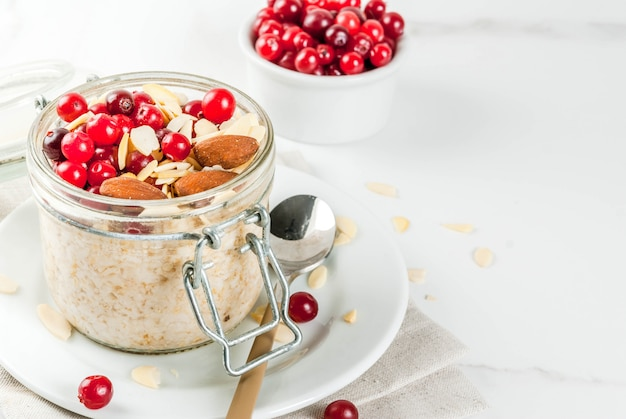 Recipe for a healthy winter breakfast, ideas for christmas morning. overnight oatmeal with almonds, cranberries, sugar. . copyspace