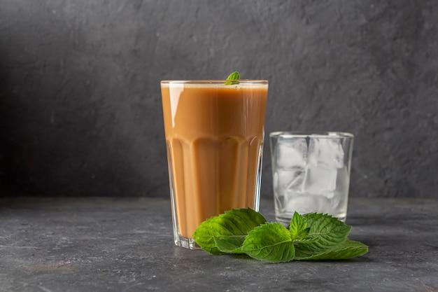 Рецепт ледяной кофе с мятой и молоком. большой стакан кофейного коктейля и стакан с кубиками льда. прохладный летний напиток на темном фоне в ключе закона. скопировать место для текста