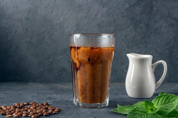 Рецепт ледяной кофе с мятой и молоком. большой стакан с черным кофе. прохладный летний напиток на темном фоне в сдержанном ключе. закройте, скопируйте место для текста.