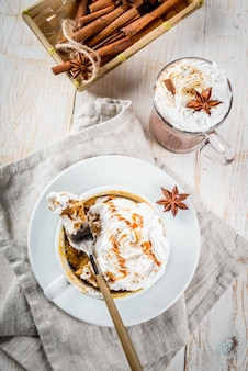 Recipes with pumpkins, fast food, microwave meal. spicy pumpkin pie in mug, with whipped cream, ice cream, cinnamon, anise. on white wooden table, with cup of hot chocolate. copyspace top view