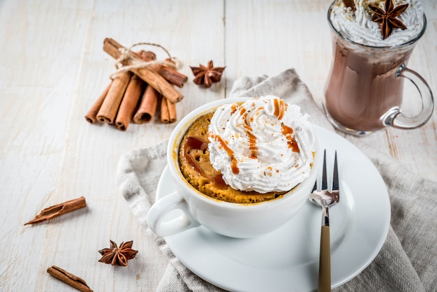 Recipes with pumpkins, fast food, microwave meal. spicy pumpkin pie in mug, with whipped cream, ice cream, cinnamon, anise. on white wooden table, with cup of hot chocolate. copyspace