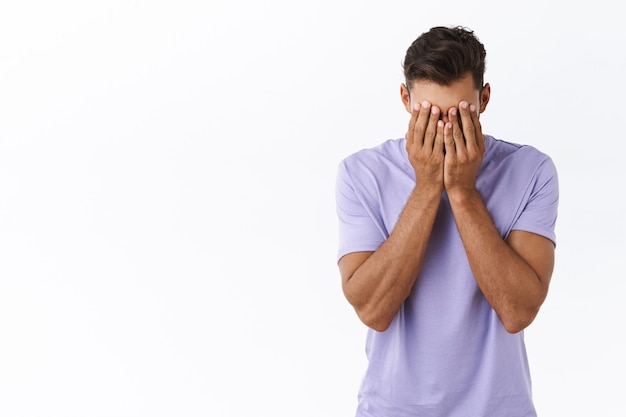 Reckless distressed, depressed young millennial guy in purple t-shirt, tired of problems, dont know how solve situation, cover face with hands, facepalm from fatigue and annoyance, white wall