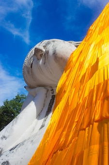 Reclining buddha statue on blue sky background in thailand.