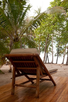 Reclining wood lounge chair on a wooden deck facing jungle trees