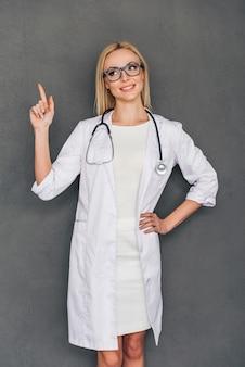 의사의 추천서. 아름다운 젊은 여성 의사가 복사 공간을 가리키고 회색 배경에 서서 미소를 지으며 시선을 돌립니다.