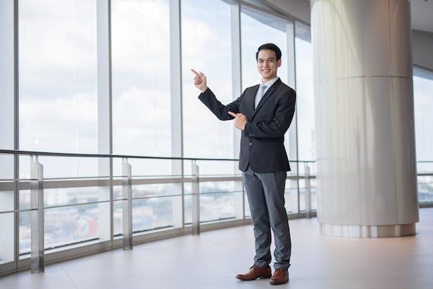 권장 사항 아시아 남자는 사업가처럼 보이고 광고에는 빈 공간 배경이 있습니다.