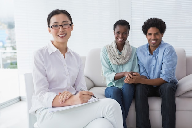 Reconciled couple smiling at camera with therapist