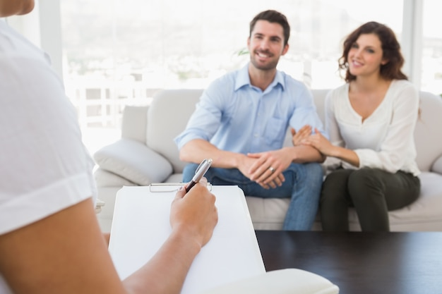 Reconciled couple smiling and talking with their therapist