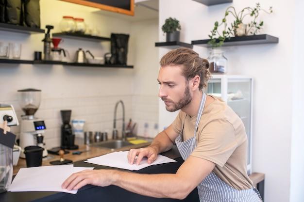 계정 조정. 카페에서 바 카운터 근처에 서있는 문서를 확인하는 프로필에 집중된 젊은 수염 난된 남자