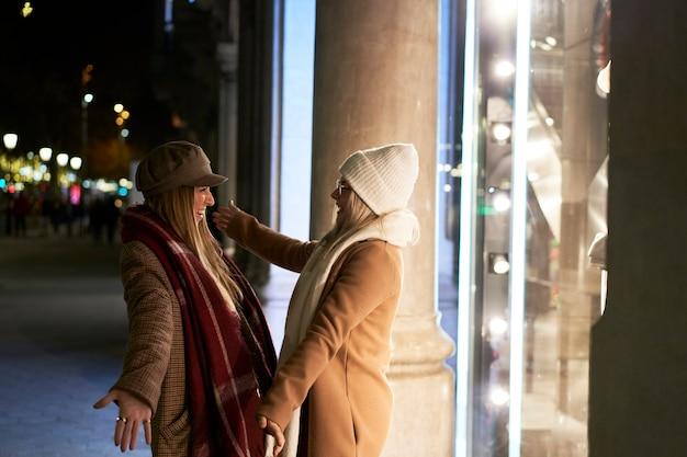 다시 만나서 행복하고 흥분된 두 젊은 여성을 다시 연결하고 열정적으로 서로를 포용합니다.