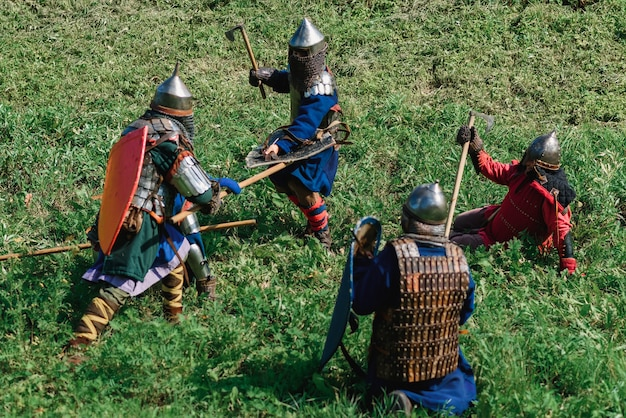 Reconstruction of medieval battle of knights in armor and weapons at the festival of onions