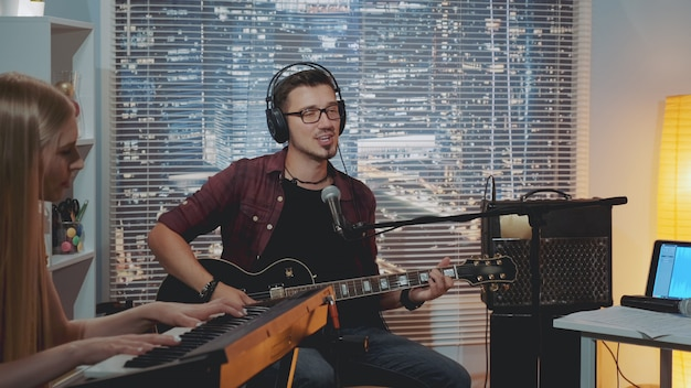 Recording hit song in home studio: young man in headphone singing and playing guitar
