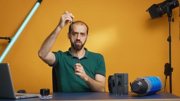 Vlogのスタジオでusbタイプcのケーブルのレビューを記録します。仕事、写真スタジオのソーシャルメディアスターおよびインフルエンサーのためのプロのスタジオビデオおよび写真機器技術