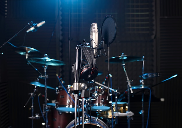 Recording studio with drum set, microphones and recording equipment.