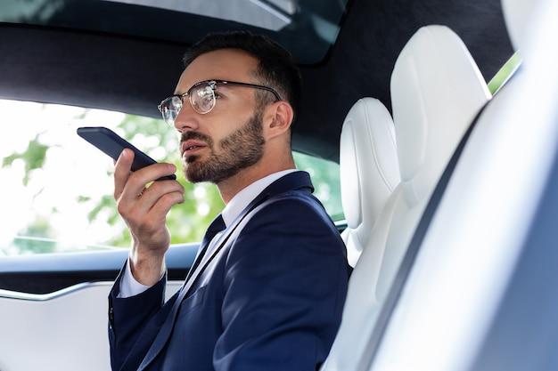 Запись голосовой почты. занятый красивый бизнесмен, записывающий голосовую почту для секретаря, сидя в машине