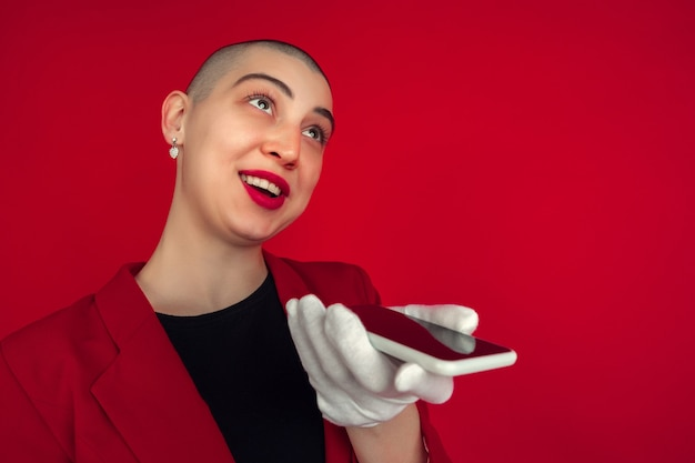 Recording voice portrait of young caucasian bald woman isolated on red studio wall.