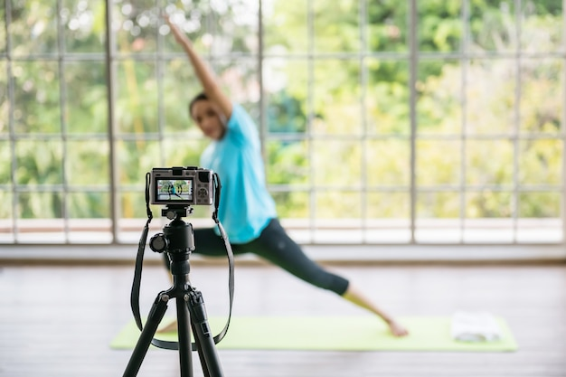 Recording yoga online training by mirrorless camera on tripod to tutorial live on internet.