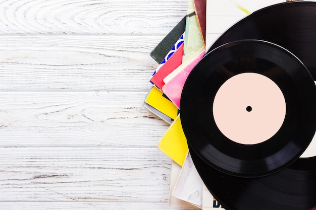 Records stack with record on top over wooden table background