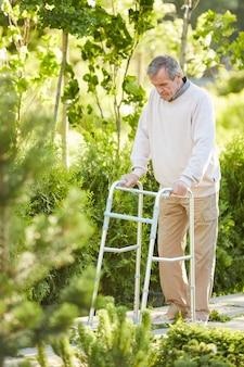 Recovering senior man using walker