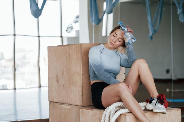 Выздоравливает при сидении на ящиках. спортивная молодая женщина имеет фитнес-день в тренажерном зале в утреннее время