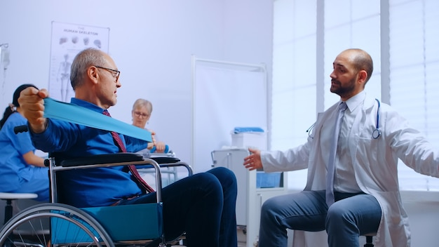 Recovery program for invalid senior persons, training with elastic band under doctor supervision in private recovery facility. invalid physiotherapy program, health care injury rehabilitation in hospi