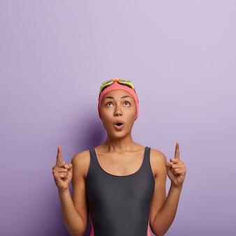 Concetto di ricreazione e pubblicità. la donna afroamericana con il fiato sospeso indica sopra