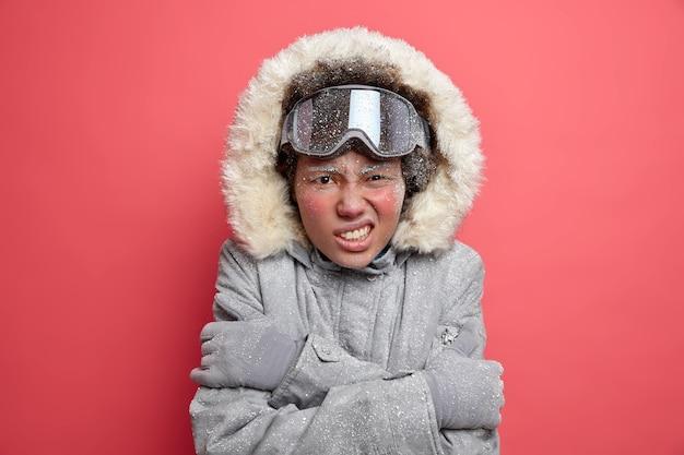 레크리에이션 및 활동적인 레저 개념. 불만족스러운 여성이 이빨을 움켜 쥐고 서리가 내린 1 월에는 매우 추위를 느끼며 몸을 껴안고 겨울에는 추운 날씨에 따뜻한 옷을 입습니다.