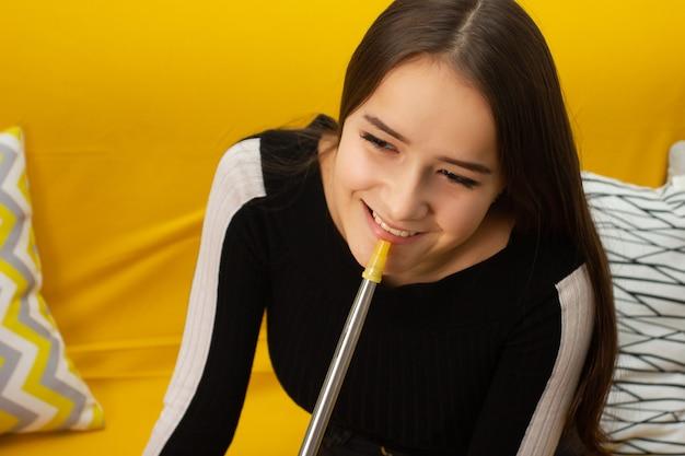 レクリエーションと娯楽。若い美しい少女は、バーで水ギセルを吸って、友達と楽しんで、笑顔で、飲んでいます
