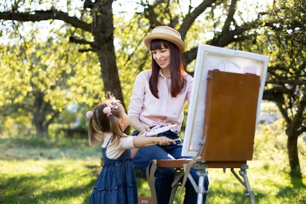 野外でのレクリエーションと家族の夏のゲーム。幼い娘と一緒に時間を楽しみ、庭でイーゼルを使って絵を教えている、笑う若い母親。