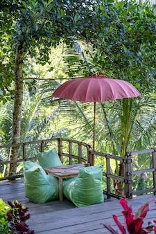 インドネシアのバリ島の晴れた日の棚田近くのレクリエーションエリアと緑の葉のヤシの木。自然と旅行のコンセプト