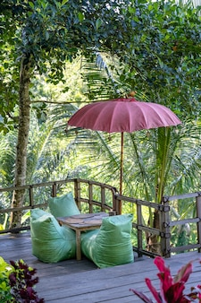 Recreation area and green leaves palm trees near rice terraces on a sunny day in bali island, indonesia. nature and travel concept