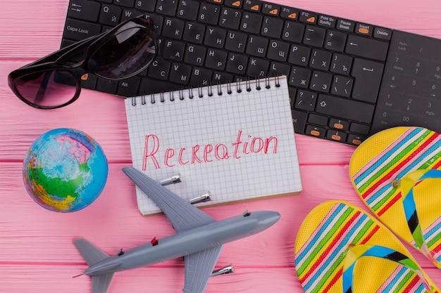女性の旅行者のアクセサリーのメガネの財布とピンクのテーブルのフリップフロップとノートブックのレクリエーション...
